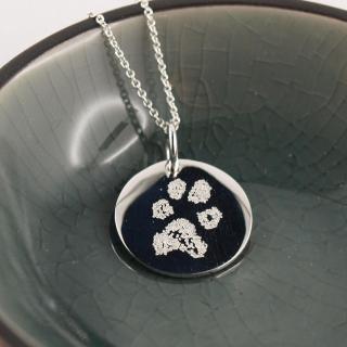 Tierpfote auf einem runden Anhaenger Silber